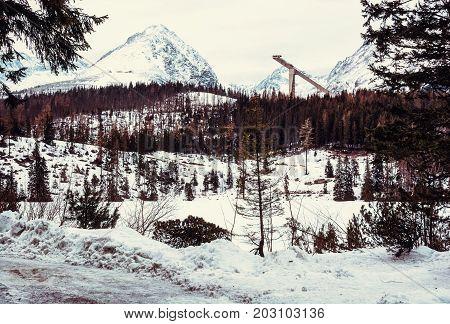 Solisko peak with springboard for ski jumping Strbske pleso Slovak republic. Winter mountains. Retro photo filter.