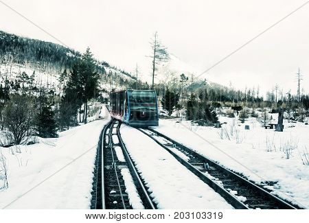 Funicular railway at High Tatras mountains in Slovak republic. Rail cable car leads from Stary Smokovec to ski and tourist resort Hrebienok. Blue photo filter.