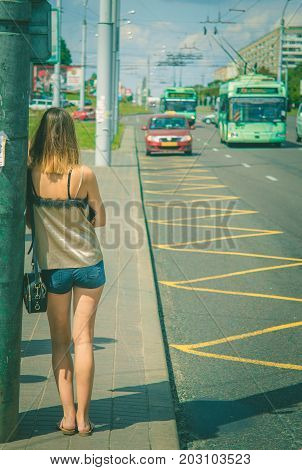 Beautiful young woman waiting for a bus.