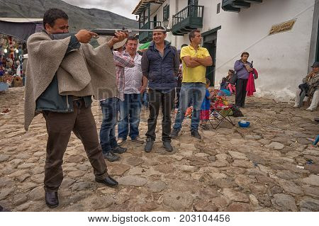 July 16 2017 Villa de Leyva Colombia: a local man wearing poncho aiming with a pellet gun during a fiesta