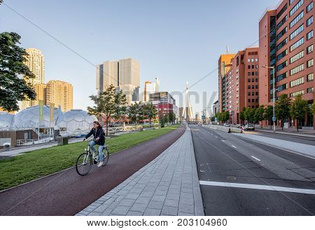 ROTTERDAM, NETHERLANDS - August 06, 2017: Cityscape view on the modern district with residential skyscrapers, floating pavillion and woman on the bicycle during the morning in Rotterdam