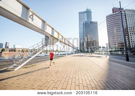 ROTTERDAM, NETHERLANDS - August 06, 2017: Sports man running in the city with modern footbridge and skyscrapers on the background during the morning in Rotterdam