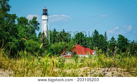 A Wisconsin lighthouse rises out of the forest looking over Lake Michigan.