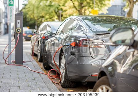 ROTTERDAM, NETHERLANDS - August 06, 2017: Tesla model S charging on the street in Rotterdam. This car is a full-sized all-electric five-door, luxury liftback, produced by Tesla, Inc