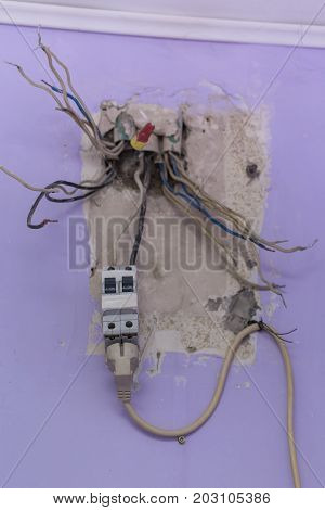 Old electrical panel switch with wires mounted in wall