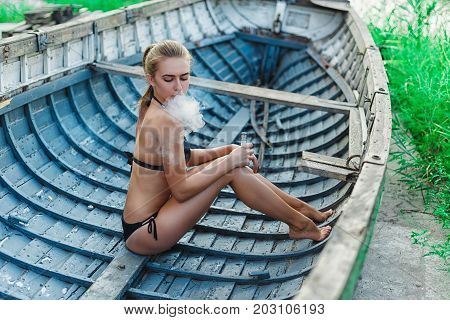 Woman Sitting In Wooden Boat And Vaping Vape Mod Device. Vaping Concept. Woman Wearing In Black Swim