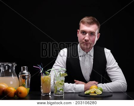 A bar counter with oranges, slices of lime, cocktails, lemon, an attractive bartender on a black background. Party, night club, cafe, entertainment concept.