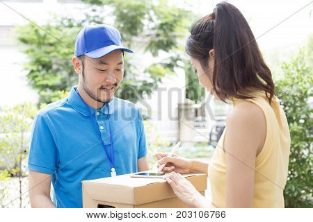 Young Asian Woman Receive Box From  Delivery Man And Sign On Smartphone. People With Delivery Concep