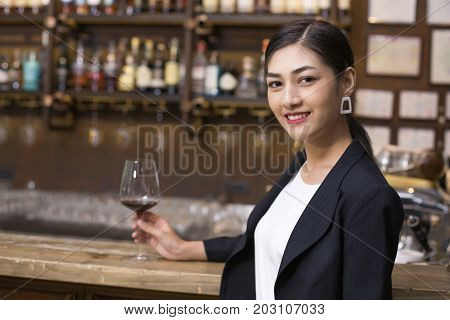 Young Asian Sommelier Woman Tasting Red Wine With Happy Emotion. The Woman Is Holding  Wineglass And
