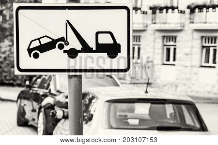 Tow away sign. No parking place. The cars are parked on prohibition parking. Traffic sign. Black and white photo.
