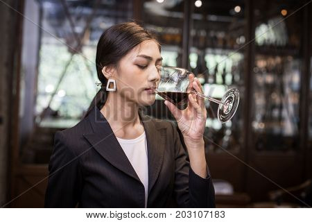 Young Asian Sommelier Woman Tasting Red Wine With Relax Emotion. The Woman Is Holding  Wineglass And