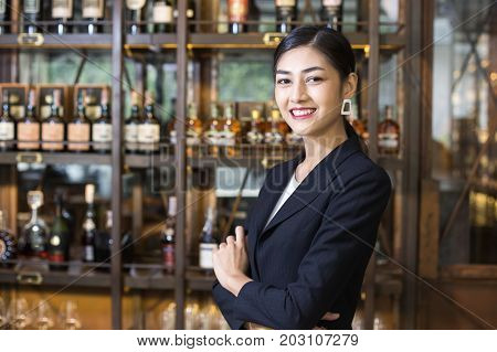 Young Asian Woman Restaurant Standing With Happy Emotion. Woman Present Wine For Customer At Bar. Wo