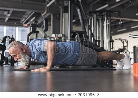 Warm up muscles. Confident senior man with beard is wearing sport clothes and doing push-ups while exercising on the floor in modern gym. Low angle