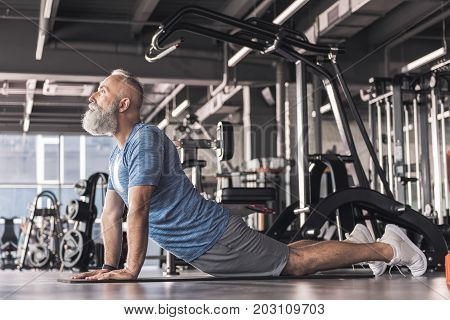 Cobra pose. Concentrated old bearded man in sportswear is doing exercises while lying on floor in modern gym with professional equipment on background
