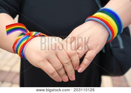 Concept of sexual minority. Female hands with rainbow wristbands  outdoors