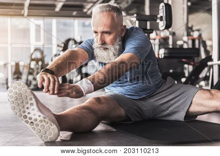 Great progress. Concentrated senior man with gray hair is doing stretching while sitting on floor in modern gym with sports equipment on background. Focus on face