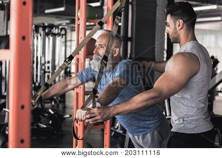 Keen on exercise. Concentrated senior bearded man is doing push-ups on trx bands with his professional trainer while standing against sport equipment in athletic club