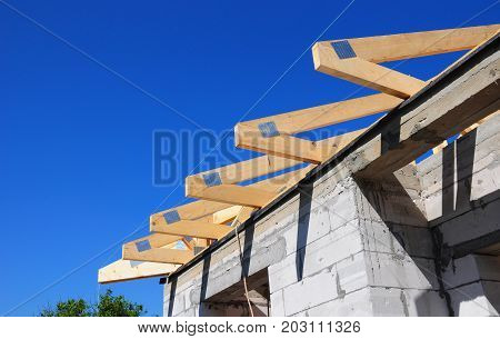 Installation of wooden beams at construction the roof truss system of the house
