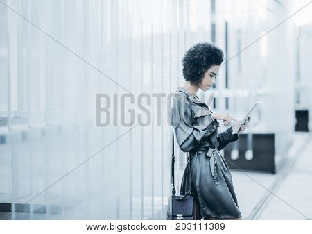 Charming young afro american business girl is standing outdoor of contemporary office near modern regular glass striped construction and using her digital tablet with copy space for your logo or text