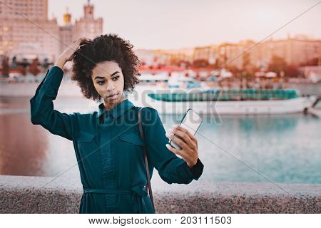 Beautiful serious young curly Brazilian girl is making selfie on frontal camera of her cell telephone while standing near granitic fencing of embankment with touristic ship passing by in background