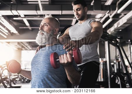 Low angle of old bearded man is doing exercises with dumbbells while sitting in sport club with professional equipment on background. Young trainer is standing behind him and touching his shoulders