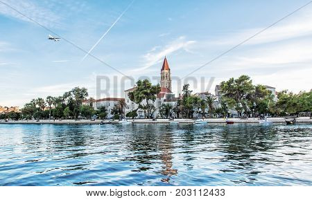 Old town Trogir with Cathedral of St. Lawrence clear water at Adriatic sea and an airplane flies to the nearby Split town. Travel destination.