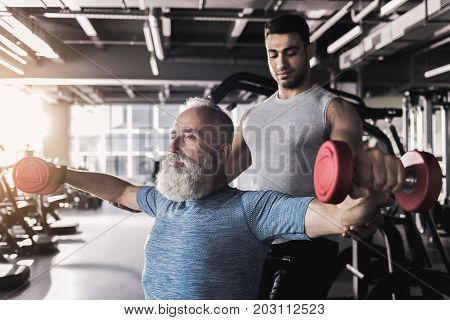Concentrated old bearded pensioner is doing lateral raise with dumbbells while sitting in modern athletic center. His professional trainer is standing behind him and controlling exercises