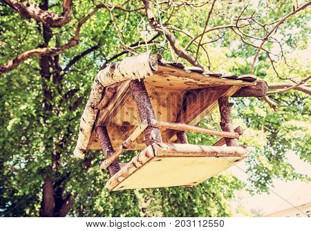 Wooden bird house hanging on the green tree. Seasonal natural scene. Ornithology theme. Detailed natural scene. Red photo filter.