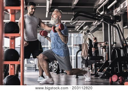 Favorite activity. Concentrated old man is doing lunge with dumbbells while having workout in modern gym with professional instructor. Copy space in the right side