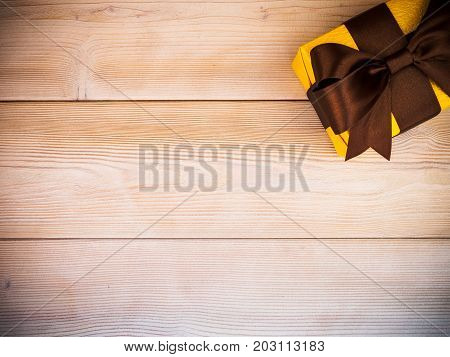 Birthday present with brown satin tape on wooden board. Holidays concept