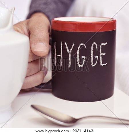 closeup of a young man with a mug with coffee or tea, where there is the text hygge, a danish and norwegian word for comfort or enjoy, which can be a whole philosophy of life