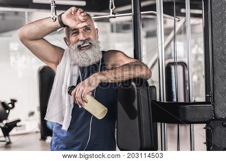 Tired and happy. Strong muscular old bearded man is listening to music through earphones with smile and holding bottle of water while wiping his brow with hand in modern gym