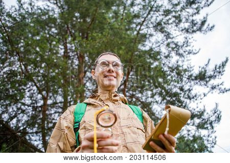 Picture from below of happy brunet with compass and notepad in autumn forest during day