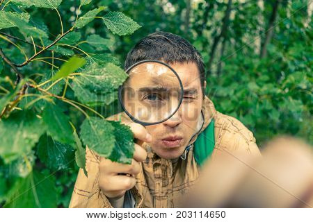 Photo of ecologist man with magnifying glass in summer forest