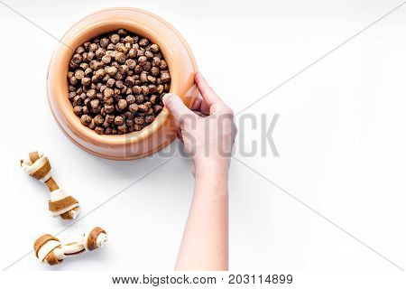 pet care with dry food for pet - dog in plastic bowl and hand on white desk background top view space for text