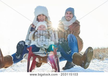 Family with child drive toboggan or sled in the snow and have fun