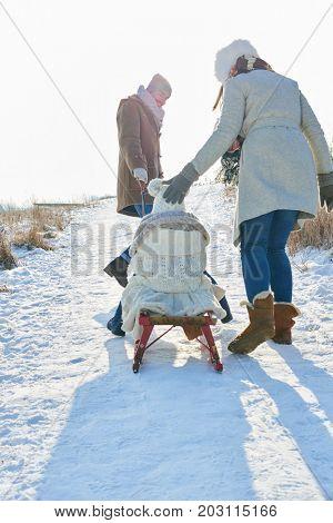 Parents pull child in winter toboggan walk in the snow