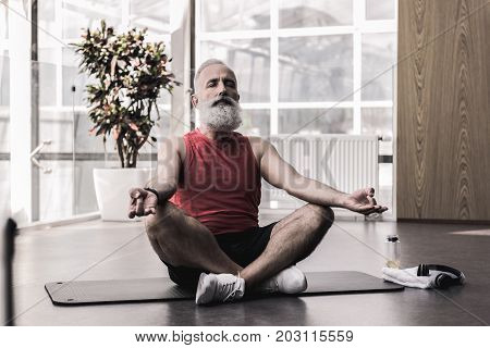 Be in harmony. Relaxed senior man with beard is keeping his eyes closed while sitting in lotus position in front of window in modern gym
