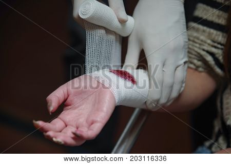 Close up of a wrist injured covered with a white gauze bandage.
