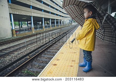 boy with an umbrella stands on the station waiting for a train. the child in a yellow raincoat standing on the railway platform. Copy space for your text
