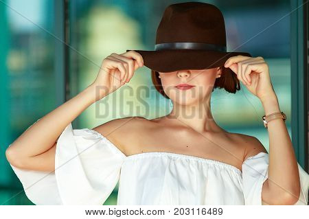 pretty girl in a hat. young beautiful woman puts on hat. hiding eyes. closeup
