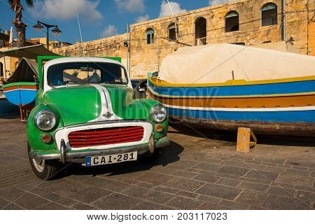 MARSAXLOKK MALTA - AUGUST 23 2017: Old Morris car parked in the harbor of Marsaxlokk. Vintage cars are used often in modern times in Malta