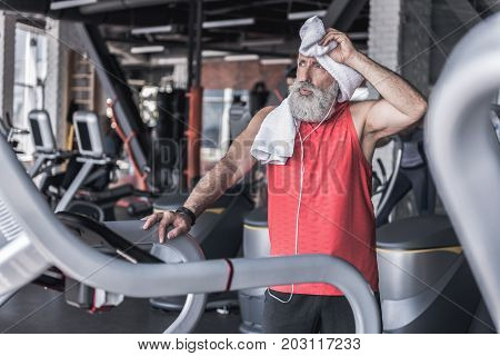 Feeling tired. Stylish old bearded man is wiping his brow with towel after intense workout on treadmill in sport center. Copy space in the left side