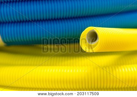 Yellow and blue corrugated plastic tube. Abstract industrial background.