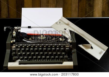 Typewriter On The Black Table. White Blank Card. Wall Of Rough Boards.