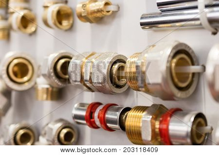 A variety of plumbing pipe connectors, corners, fittings, nipples. Abstract industrial background