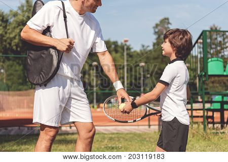 Curious son is holding racquet and looking at father with smile. Dad teaching young male person. Focus on special equipment in their hands
