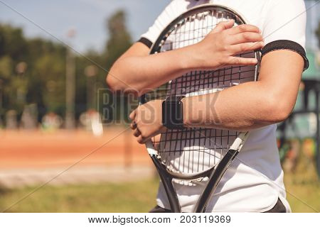 Boy is clenching tennis racquet and standing outside. Close up of necessary equipment. Copy space on left side
