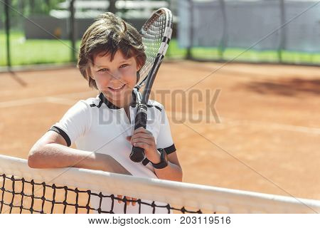 Glad boy is holding tennis racket and looking at camera with smile. He standing near grid. Portrait. copy space on right side