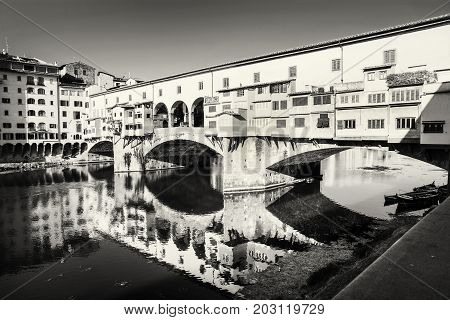Beautiful Ponte Vecchio is mirroring in the river Arno Florence Tuscany Italy. Black and white photo. Travel destination.